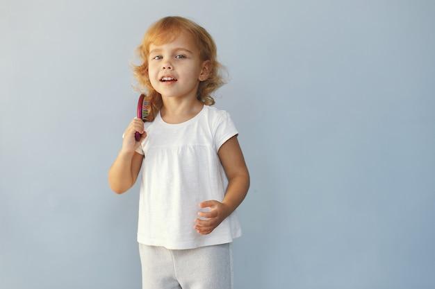 Śliczny małej dziewczynki obsiadanie w studiu na błękitnym tle