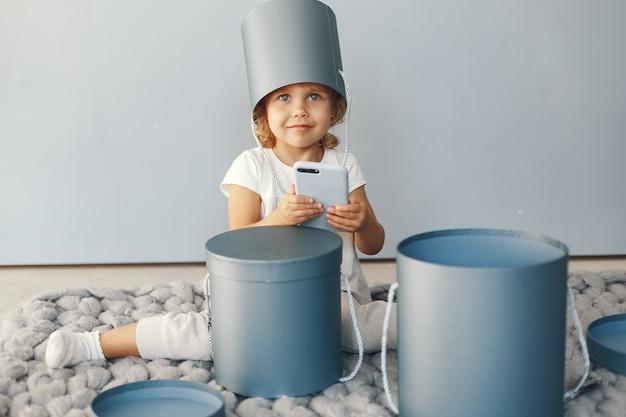 Śliczny małej dziewczynki obsiadanie w studiu z teraźniejszości pudełkiem