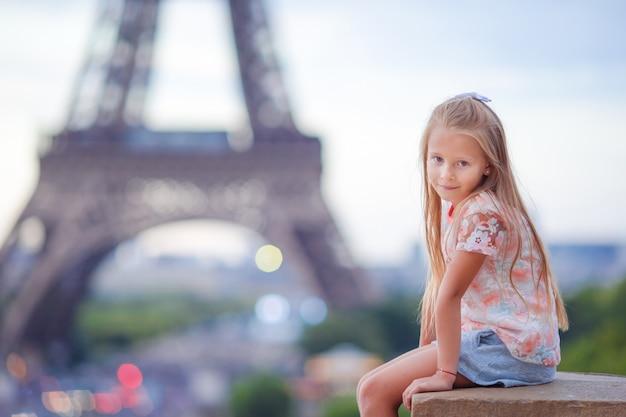 Śliczny małej dziewczynki tło wieża eifla podczas wakacji w paryż