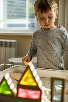 Śliczny maluch bawiący się w samorozwoju w domu kinetyczna piaskownica wykorzystuje metodę maria montessori
