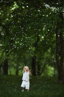 Śliczny maluch chłopiec spacerujący po zielonej trawie pod kwitnącą wiśnią w parku miejskim w ciepły wiosenny dzień.