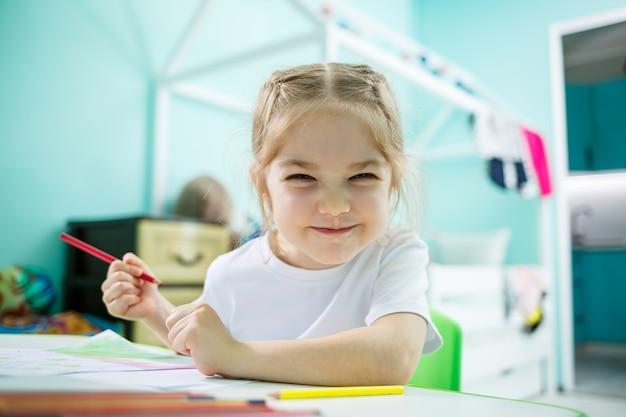 Śliczny maluch dziewczyna rysunek ołówkami w domu siedzi przy stole. kreatywne dziecko siedzi w pokoju, uczy się rysować. toddler dziewczyna odrabianiu lekcji w domu.