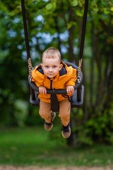 Śliczny maluch o niebieskich oczach i krótkich blond włosach, huśtający się na huśtawkach na placu zabaw - jesienny dzień