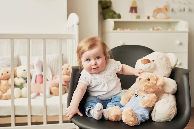 Śliczny maluch siedzi na krześle w pobliżu zabawek