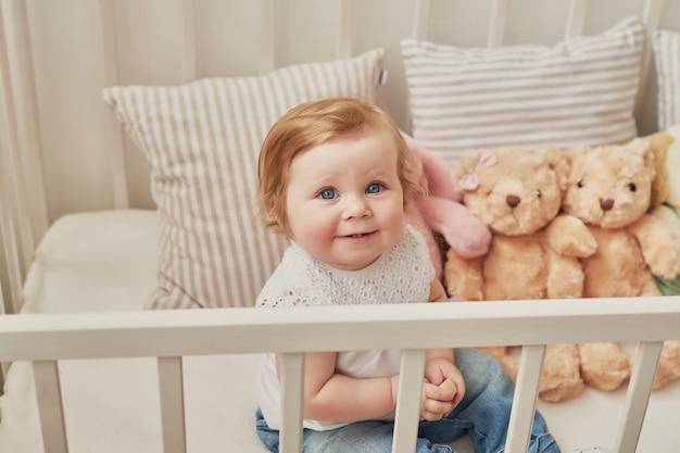 Śliczny maluch siedzi w swoim łóżeczku w pobliżu zabawek