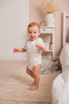 Śliczny maluch uczy się chodzić przez okno łóżka w domu. pierwsze kroki chłopca uczącego się chodzić w białej słonecznej sypialni. wnętrze pokoju dziecinnego