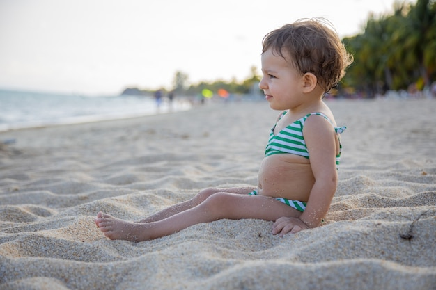 Śliczny maluch w kostiumie kąpielowym siedzi na tropikalnej, piaszczystej plaży nad ciepłym morzem w słońcu.