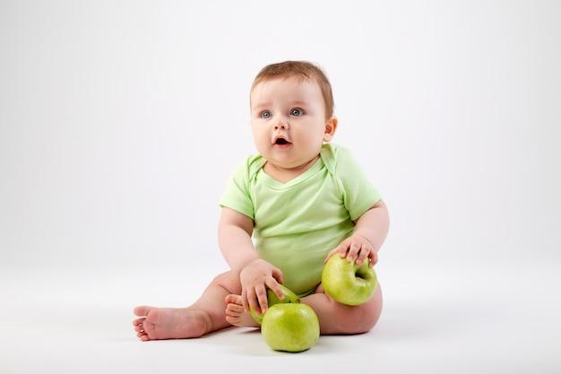Śliczny maluch w zielonym body siedzi z zielonymi jabłkami