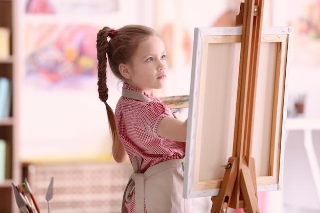 Śliczny mały artysta malujący obraz w studio