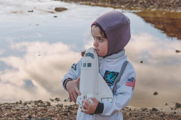Śliczny mały astronauta z zabawką