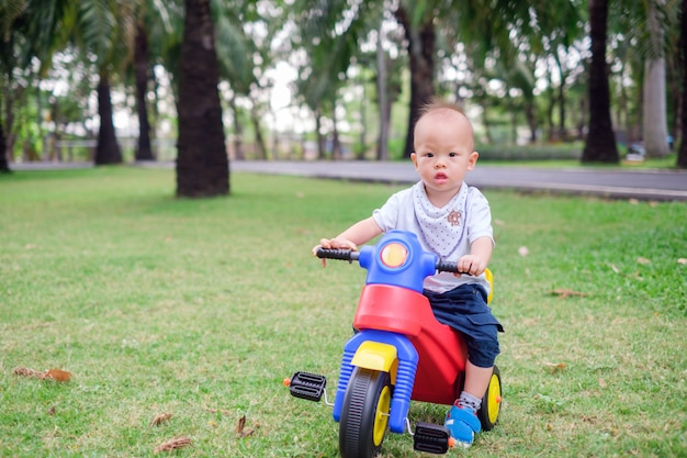 Śliczny mały azjatycki 1-letni berbeć chłopiec dziecko jedzie jego trójkołowiec w lato parku