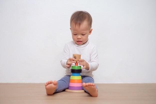 Śliczny mały azjatycki 18-miesięczny maluch chłopiec dziecko bawi się kolorową drewnianą piramidą / pierścieniem do układania. dzieciak bawić się z edukacyjną zabawką odizolowywającą na biel ścianie z kopii przestrzenią