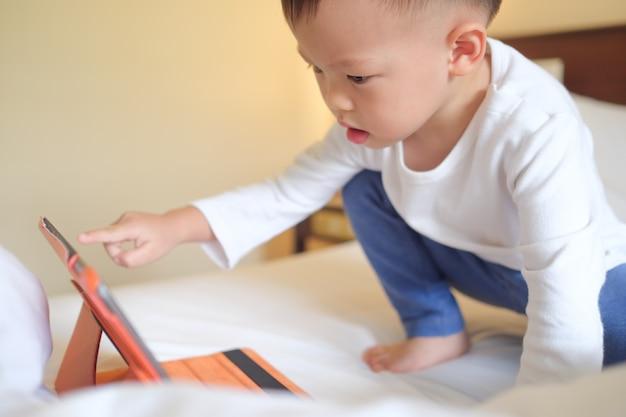 Śliczny mały azjatycki 2-3 lat berbecia chłopiec dziecka obsiadanie w łóżku ogląda wideo od pastylka komputeru osobistego