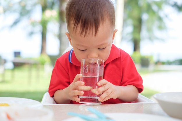Śliczny mały azjatycki berbeć chłopiec dziecka obsiadanie w wysokim krześle trzyma on i pije szkło woda przy restauracją w miejscowości nadmorskiej