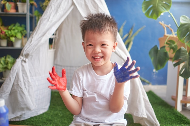 Śliczny mały azjatycki chłopiec dziecka palca obraz z rękami i akwarelami w domu, kreatywnie sztuka dla dzieciaka pojęcia