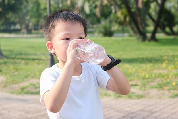 Śliczny mały azjatycki chłopiec dziecko pije czystą wodę z butelki wielokrotnego użytku na naturze w parku