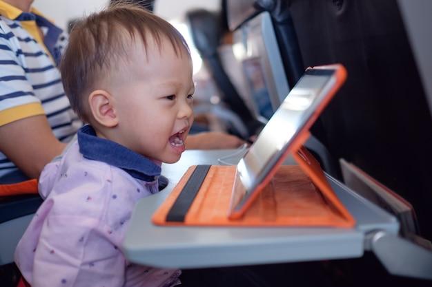 Śliczny mały azjatycki maluch chłopiec dziecko przy użyciu komputera typu tablet oglądając bajki podczas lotu samolotem