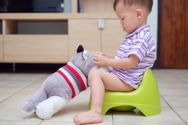 Śliczny mały azjatycki maluch chłopiec dziecko siedzi na nocniku bawi się swoim psem pluszową zabawką