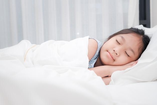 Śliczny mały azjatykci dziewczyna śpi na łóżku w sypialni