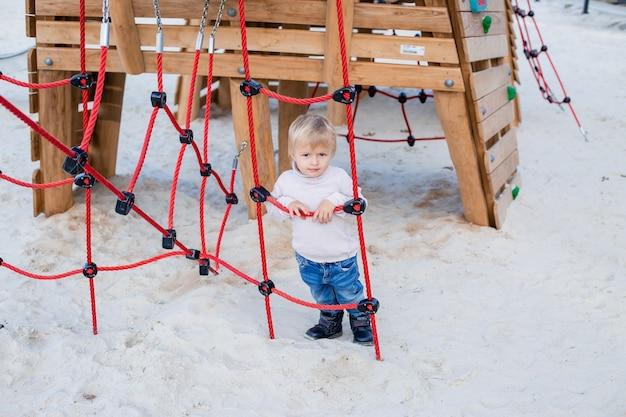 Śliczny mały blond chłopiec w swetrze z dzianiny bawi się jesienią w miasteczku dla dzieci w parku miejskim