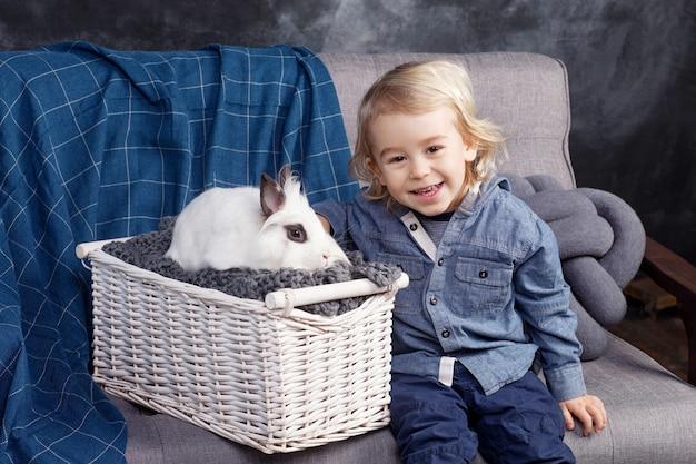 Śliczny mały chłopiec bawi się białym królikiem. chłopiec się śmieje, patrzy w kamerę