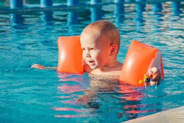 Śliczny mały chłopiec bawi się w odkrytym basenie w upalny letni dzień dzieci uczą się pływać szczęśliwe dziecko z pomarańczowymi pływakami ochrona pomocy pływackiej dla dziecka rodzinne wakacje