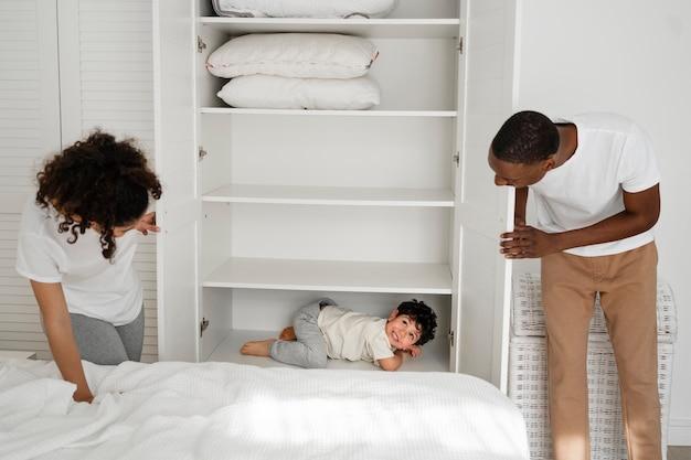 Śliczny mały chłopiec chowający się w szafie podczas płacenia z rodzicami