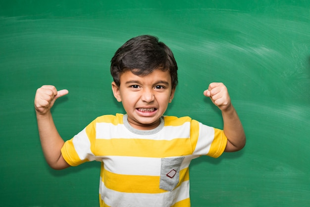 Śliczny mały chłopiec dziecko indyjskiej szkoły w ręku rozciągnięty poza na zielonej tablicy lub tle tablicy kredowej, trzymając książki, puchar zwycięstwa itp., na białym tle