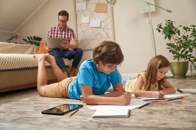 Śliczny mały chłopiec i dziewczynka leżący na drewnianej podłodze i rysujący kolorowymi kredkami, podczas gdy ich