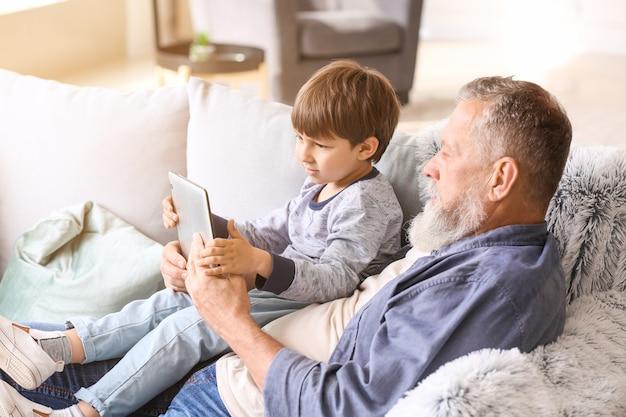 Śliczny mały chłopiec i jego dziadek z komputerem typu tablet w domu