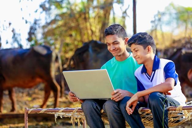 Śliczny mały chłopiec indyjski / azjatycki studiujący lub grający z laptopem