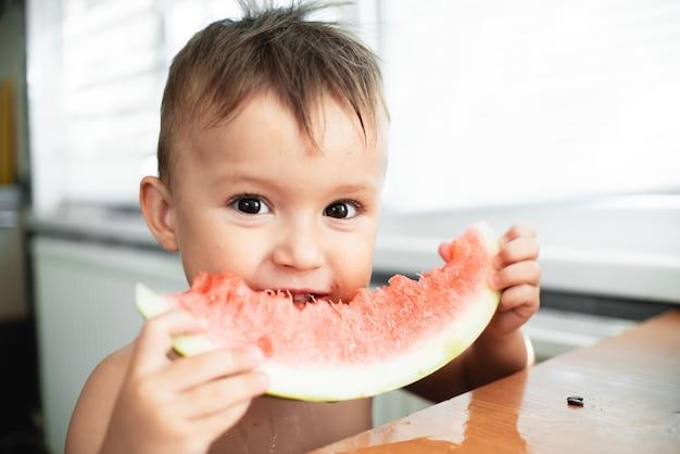 Śliczny mały chłopiec je arbuza w kuchni, bardzo słodki