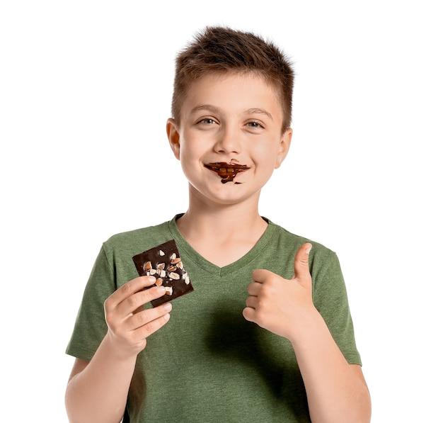 Śliczny mały chłopiec je czekoladę na białym