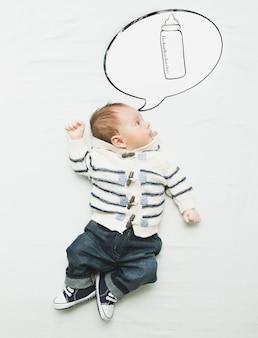Śliczny mały chłopiec leżący na łóżku i marzący o butelce z mlekiem