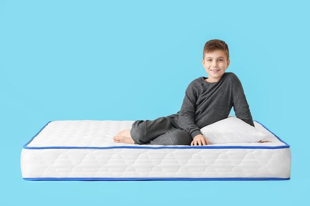 Śliczny mały chłopiec na materacu przeciwko kolorowi