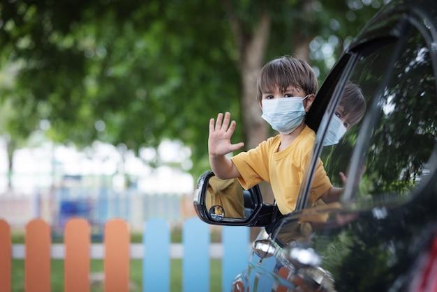 Śliczny mały chłopiec noszący maskę ochronną w samochodzie po szkole podczas epidemii