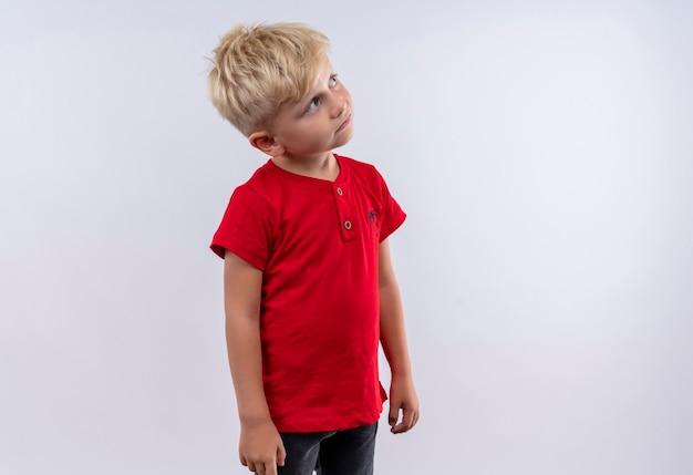 Śliczny mały chłopiec o blond włosach i niebieskich oczach ubrany w czerwoną koszulkę patrząc na białą ścianę