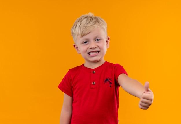 Śliczny mały chłopiec o blond włosach i niebieskich oczach ubrany w czerwoną koszulkę pokazujący kciuki do góry, patrząc na żółtą ścianę