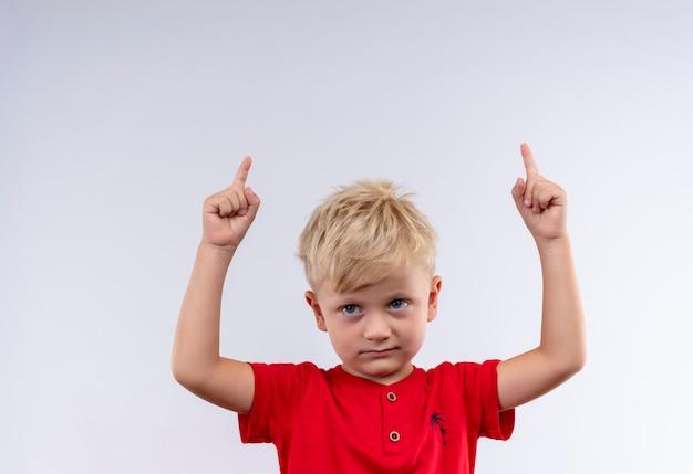 Śliczny mały chłopiec o blond włosach i niebieskich oczach ubrany w czerwoną koszulkę skierowaną w górę z palcami wskazującymi patrząc z boku na białej ścianie