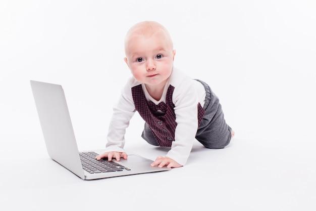 Śliczny mały chłopiec obsiadanie na białym tle