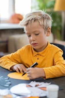 Śliczny mały chłopiec rysujący obraz symbolu halloween