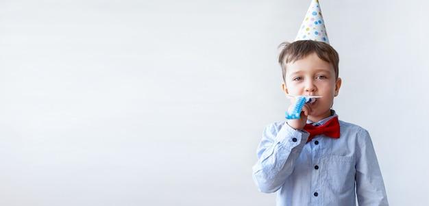 Śliczny mały chłopiec w czerwonej muszce z róg strony kapelusza. przyjęcie urodzinowe.