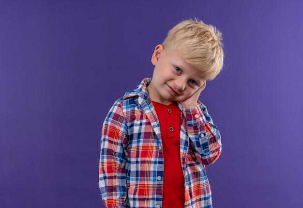 Śliczny mały chłopiec z blond włosami w kraciastej koszuli, trzymając rękę na twarzy, patrząc na fioletową ścianę