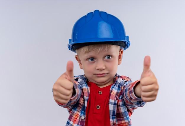 Śliczny mały chłopiec z blond włosami w kraciastej koszuli w niebieskim hełmie pokazując kciuki do góry na białej ścianie