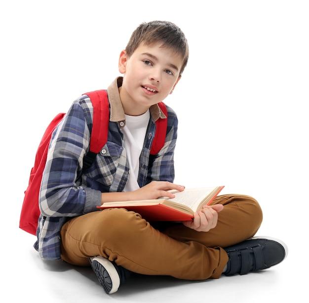 Śliczny mały chłopiec z czerwonym plecakiem czyta książkę, na białym tle