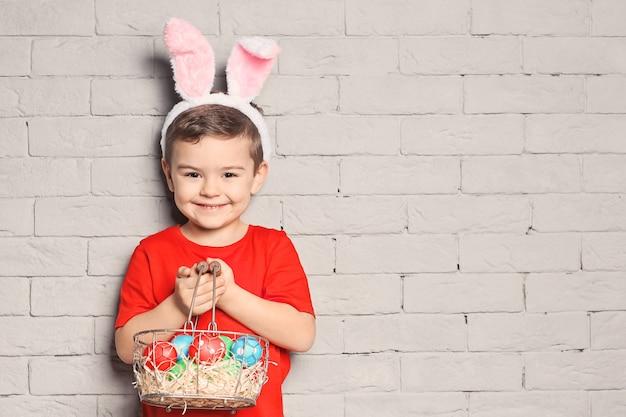Śliczny mały chłopiec z uszami królika trzymający kosz pełen pisanek na ceglanym murze