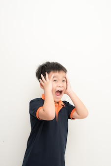 Śliczny mały chłopiec zakrywający uszy rękami, na białym tle