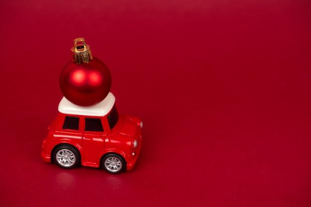 Śliczny mały czerwony samochód z czerwoną boże narodzenie piłką