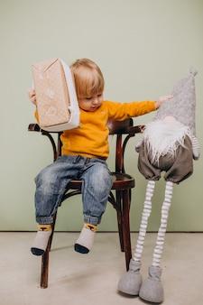 Śliczny mały czerwony włosiany chłopiec obsiadanie w krześle z bożymi narodzeniami bawi się