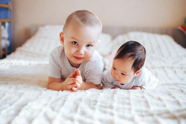 Śliczny mały dziecko z starszym bratem kłama na łóżku w domu
